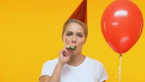 Signora turbata in pallone della tenuta del cappello di compleanno e soffiare in corno del partito, solitudine archivi video