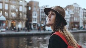 Signora turistica caucasica emozionante che gode di vecchia città La femmina con capelli lunghi in cappello alla moda filma la vi video d archivio