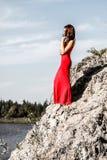 Signora in un vestito rosso sul bordo del fiume fotografie stock