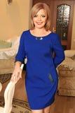 Signora in un vestito vicino alla tavola fotografia stock