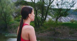 Signora in una meditazione di pratica di yoga degli abiti sportivi comodi in mezzo a paesaggio di stupore accanto al di stupore video d archivio