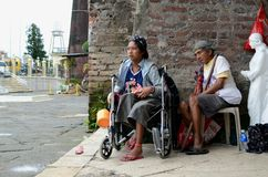 Signora, uomo cieco accanto al mendicante disabile in sedia a rotelle al portale del portone dell'iarda della chiesa immagini stock