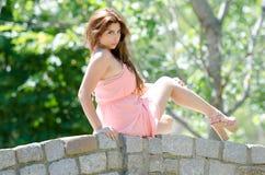Signora in vestito e tacchi alti rosa fuori, sedendosi su un ponte di pietra Immagini Stock Libere da Diritti