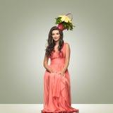 Signora in vestito rosso con il canestro del fiore sui sorrisi capi Fotografia Stock