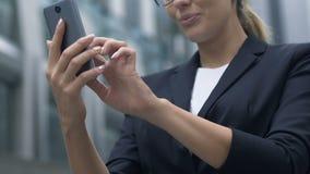 Signora in vestito soddisfatto con velocità veloce di accesso Internet mobile, app video d archivio