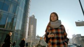 Signora Walking nel centro urbano e mandare un sms sul suo Smartphone stock footage