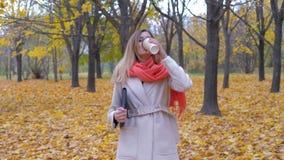 Signora Walks On The Autumn Park Holding una cartella o un caffè di bevanda e del computer portatile video d archivio