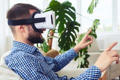 Signore alla moda negli occhiali di protezione di realtà virtuale che si siedono sul sofà Immagine Stock Libera da Diritti