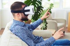 Signore atletico in vetri di realtà virtuale che si siedono sul sofà Immagine Stock