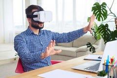 Signore attraente in vetri di VR che orientano nello spazio che si siede alla tavola Fotografia Stock