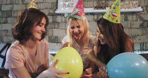 Signore carismatiche del ritratto tre davanti alla macchina fotografica che celebrano la festa di compleanno a casa facendo uso d stock footage