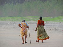 Signore che prendono una passeggiata sulla spiaggia Immagini Stock Libere da Diritti