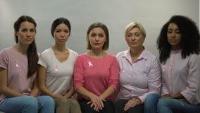 Signore con i nastri rosa che guardano in camera, pazienti di cancro al seno del supporto morale stock footage