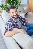 Signore con il sorriso piacevole in camicia a quadretti che si appoggia indietro oh Immagini Stock Libere da Diritti
