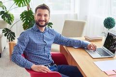 Signore delizioso che si siede alla tavola e che lavora con il computer portatile Immagini Stock