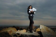 Signore di affari che si levano in piedi sulle rocce dal mare, agai Fotografia Stock Libera da Diritti
