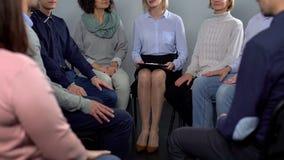 Signore ed uomini che parlano con lo psicologo femminile, sessione di terapia di riabilitazione immagine stock