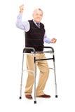 Signore maturo felice con il camminatore che gesturing felicità Fotografia Stock