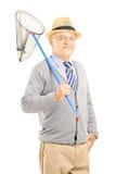 Signore maturo sorridente che posa con una rete della farfalla Fotografie Stock Libere da Diritti
