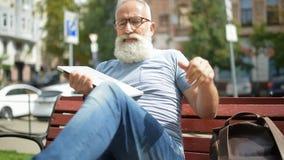 Signore senior avanzato che si rilassa sul banco con il computer portatile stock footage