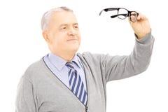 Signore senior che tiene un paio dei vetri Fotografie Stock