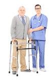 Signore senior con il camminatore che posa accanto a medico Immagini Stock Libere da Diritti