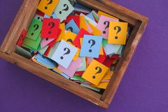 Signos de interrogación en una caja de madera Imagenes de archivo
