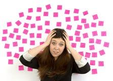 Signos y manos pegajosos de interrogación de las notas del rosa de la mujer joven en su cabeza Fotos de archivo libres de regalías