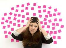 Signos y manos pegajosos de interrogación de las notas del rosa de la mujer joven en su cabeza Imagen de archivo libre de regalías