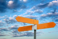 Signpost. With three blank arrows in front of cloudy sky stock photography