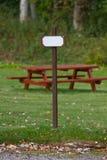Signpost ao lado do banco de parque Imagem de Stock