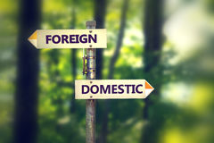 Signpost with arrows pointing in opposite directions Foreign and Domestic stock photo