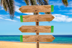 Signpost on the beach palm. Wooden signpost in the meadow with copyspace on the beach and palms stock images