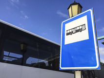 Signpost Bus Station. Signpost bus station, bus stop with bus against blue sky Royalty Free Stock Photography