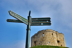 Signpost And Cliffords Tower. A signpost and Cliffords Tower against blue sky showing the quatrefoil design of the keep and the distinctive shape of the Stock Image