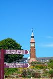 Signpost and clock tower, Seaton. royalty free stock photography