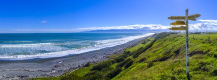 Signpost close to a sea shore. Signpost standing on top of a hill above a beach in souther New Zealand stock photos