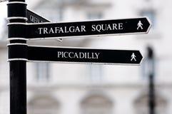 Signpost della via di Londra con il quadrato di Trafalgar Immagine Stock