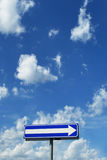 Signpost - a direction under blue cloudy sky Royalty Free Stock Photography