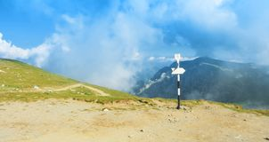A signpost direction white sign arrow near the tracking path at. The peak top of the mountain showing the right hiking direction way route trail and a panoramic Stock Photos