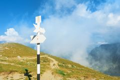 A signpost direction white sign arrow near the tracking path at Royalty Free Stock Image