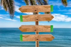 Signpost on the island. Wooden signpost in the meadow with copyspace on the ocean and palms background stock photo