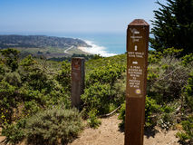 Signpost at junction of grey whale cove trail and old pedro mountain trail. With view of montara beach and Montara, California, USA, and HIghway One, PCH stock photography