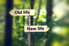 Signpost in a park with arrows old and new life pointing in two opposite directions. Signpost with arrows old and new life pointing in two opposite directions royalty free stock photo