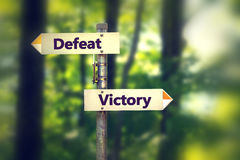 Signpost in a park with arrows pointing in opposite directions Victory and Defeat stock photography