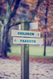 Signpost in a park with arrows pointing two opposite directions Stock Photo