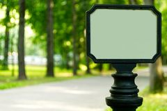 Signpost in the park. Blank informational board in the city park. Signpost on the footpath royalty free stock image