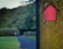 Signpost Pointing The Way. A Red Arrow On A Sign Post In A Park Shows The Way Forward Royalty Free Stock Image