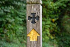Wooden signpost with cross. Signpost for the Saints´ Way with a black cross and an yellow arrow. The Saints´ way is a footpah which runs from Padstow to stock images