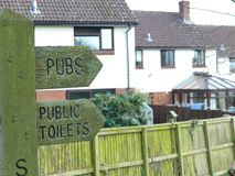 A signpost in Sampford Peverell, Devon, directing towards the pubs and toilets royalty free stock photo